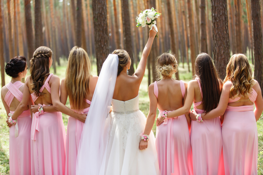 Line of bridesmaids in pink bridesmaid dresses with bride in the middle holding up her bouquet