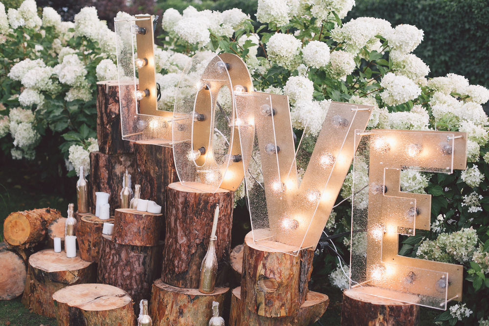 Light up Love Sign on tree stumps with white flowers in background